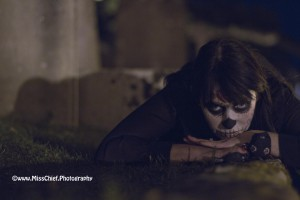 halloween lady laying down in front of tomb